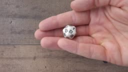 Hand showing a white 20 sided dice, up close, 4k. Flat lay, static isolated.