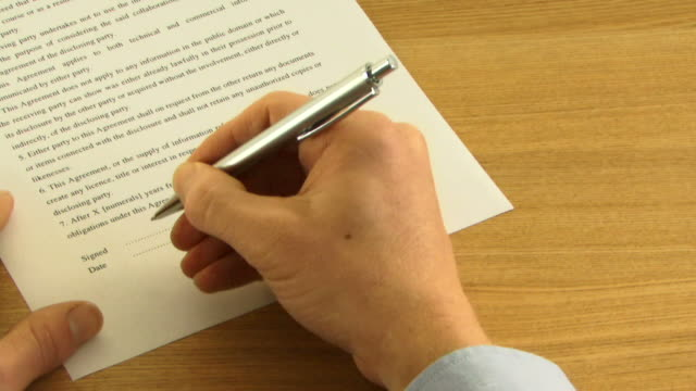 WS, Hand signing contract on table with pen
