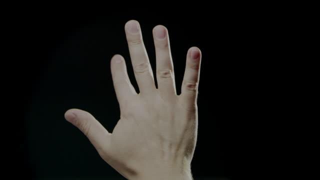 stockvideo's en b-roll-footage met hand tekenen taal slowmotion kaukasische menselijke zwarte achtergrond - handpalm