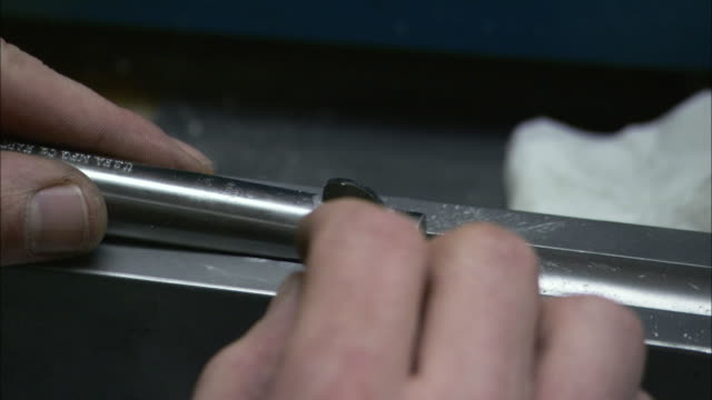 a hand solders a gun sight onto the barrel while the gun is under construction. - gun barrel stock videos & royalty-free footage