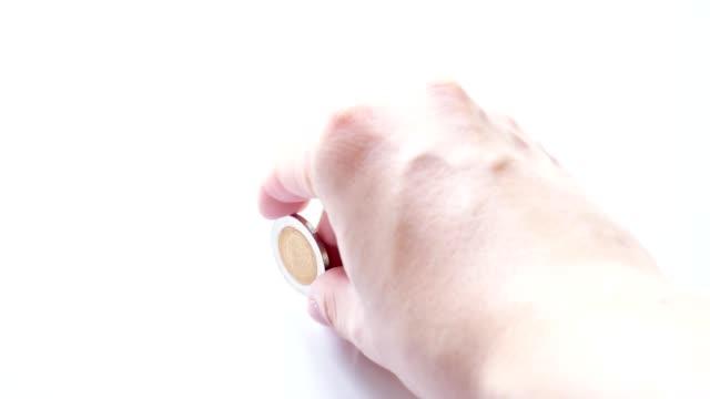 die Hand Spinnen Münze auf weißem Hintergrund
