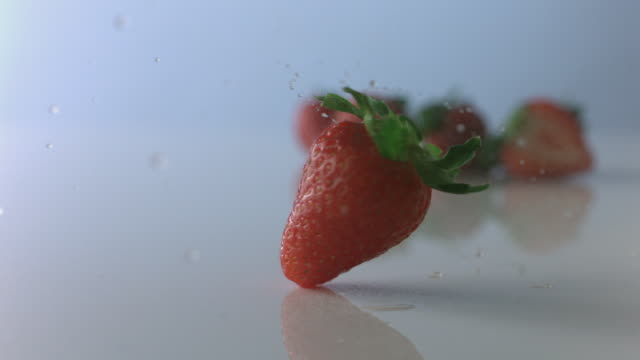 stockvideo's en b-roll-footage met hand spins strawberry and it twirls like a top through mist on white surface - vijf dingen