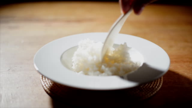 hand spoon out steamed rice.