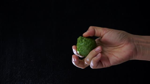 黒い背景にベルガモットオイルを絞る手 - ベルガモット点の映像素材/bロール