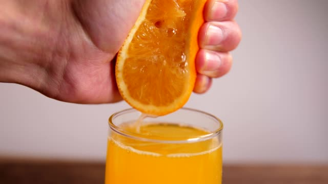 hand squeezing fresh orange juice - orange juice stock videos & royalty-free footage