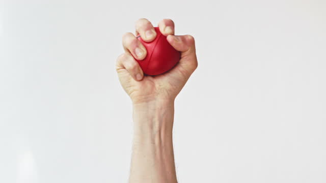 hand squeezing red stress ball - human finger stock videos & royalty-free footage