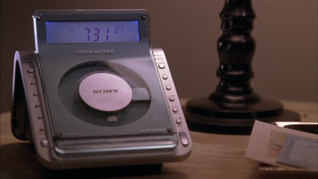 A hand starts a CD in a bedside clock radio.