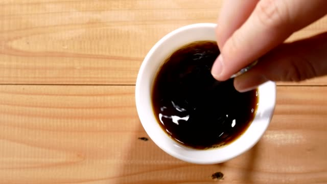 hand stirring black coffee in a cup and hand picking up on wooden table