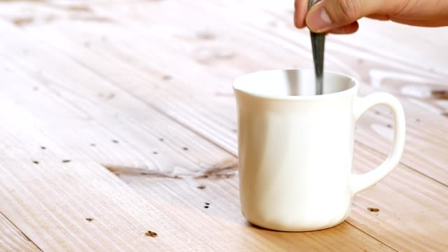hand stirring black coffee in a white cup and picking up on wooden table - mug stock videos and b-roll footage