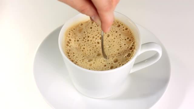stockvideo's en b-roll-footage met hd slow motion: hand stirring cappuccino - foam hand