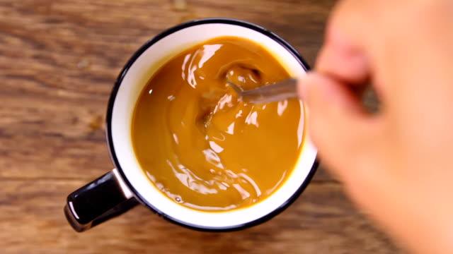 スプーンでコーヒーをかき混ぜる手 - 混ぜる点の映像素材/bロール