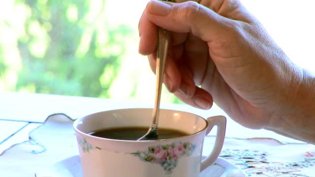 Hand stirring coffee