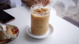 Hand Stirring tasty ice coffee.