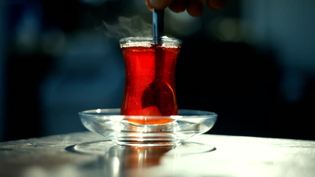 hand stirring turkish black tea with special cup on a sidewalk tea house table with unrecognizable blurry people on the background - black tea stock videos & royalty-free footage