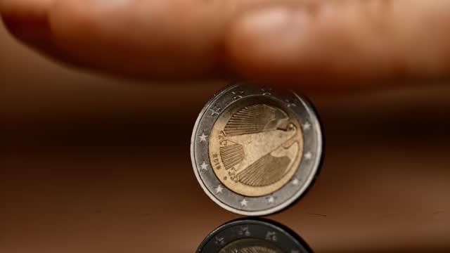 slo mo ld hand stoppt eine sich drehende euro-münze - geldmünze stock-videos und b-roll-filmmaterial