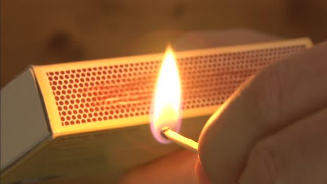 vídeos de stock e filmes b-roll de a hand strikes a match on a matchbox. - caixa de fósforos