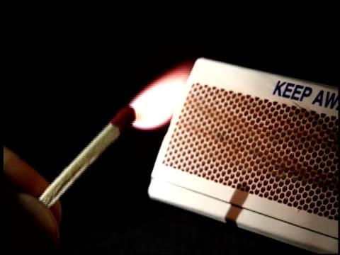 vídeos de stock e filmes b-roll de a hand strikes and lights a match on the side of a matchbox. - caixa de fósforos