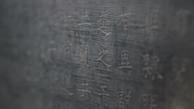 a hand strokes chinese characters on a stone tablet. - carving craft product stock videos & royalty-free footage
