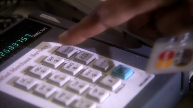 a hand swipes a credit card through a card reader several times and presses buttons on the reader. - punch card reader stock videos & royalty-free footage