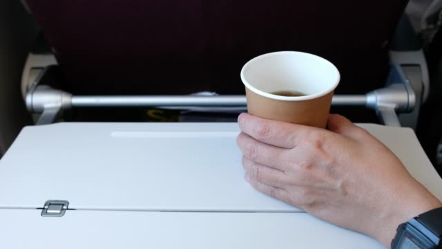 hand take out coffee cup from food tray infront of airplane seat while traveling - coffee cup stock videos & royalty-free footage