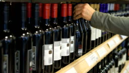 Hand takes a bottle of wine from the shelf