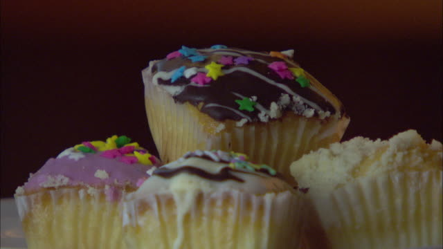 a hand takes an iced cupcake from a pile. - cream cake stock videos & royalty-free footage