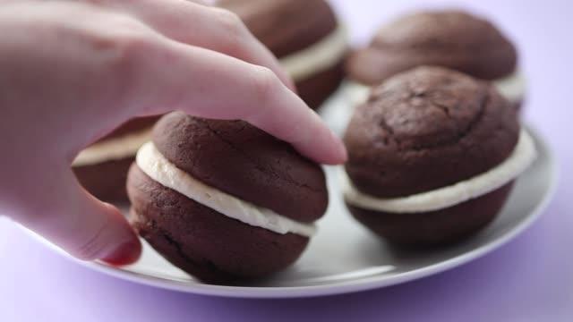 vídeos y material grabado en eventos de stock de a hand taking a chocolate whoopie pie from a plate - pastel dulce