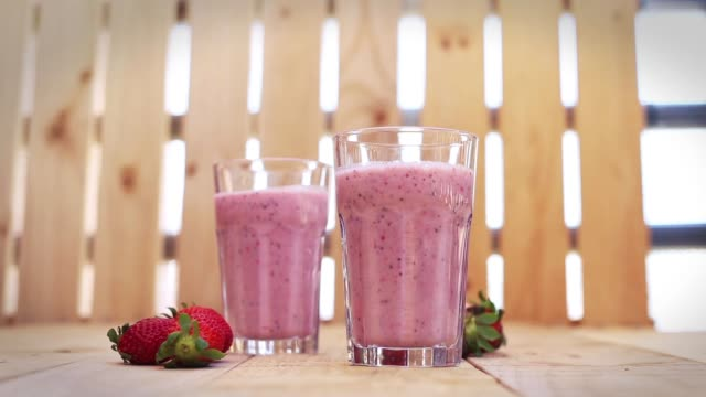 a hand taking a freshly made strawberry smoothie - strawberry milkshake stock videos & royalty-free footage