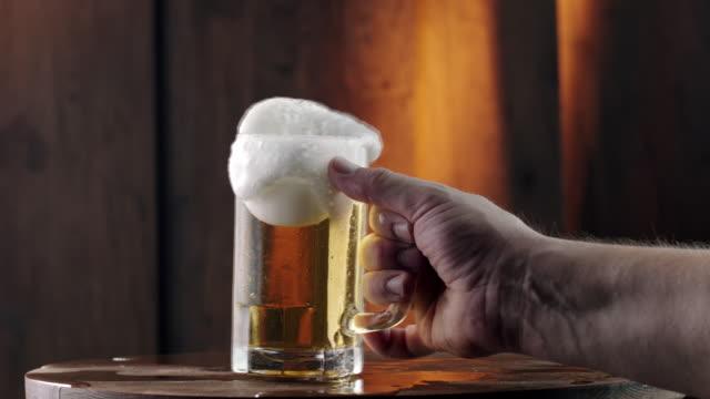 Hand taking mug full of beer