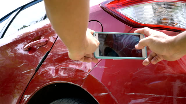 hand taking photo at scratched of vehicle's paint skin by mobile phone. - handheld stock videos & royalty-free footage