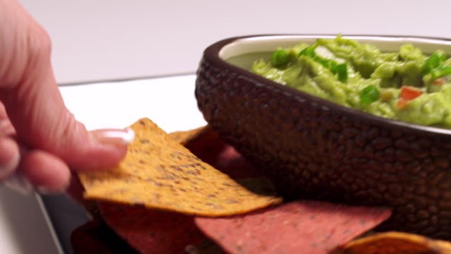 ms tu hand taking tortilla chip from serving plate and dips it into bowl of guacamole / los angeles, california, united states - dipping stock videos & royalty-free footage
