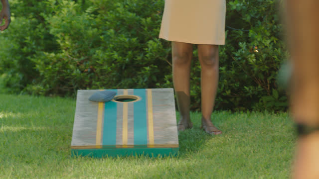 cu of hand throwing bag on cornhole board - toy stock videos & royalty-free footage