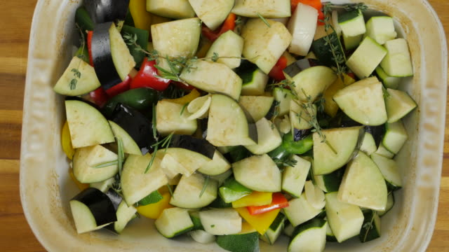 hand tossing vegetable with olive oil for roasting