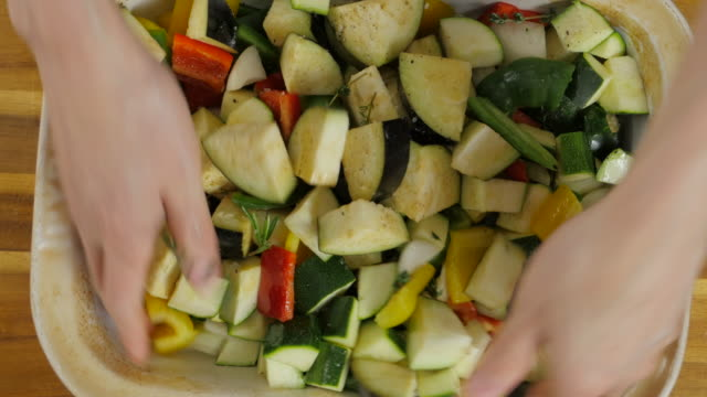 hand tossing vegetable with olive oil for roasting - courgette stock videos and b-roll footage