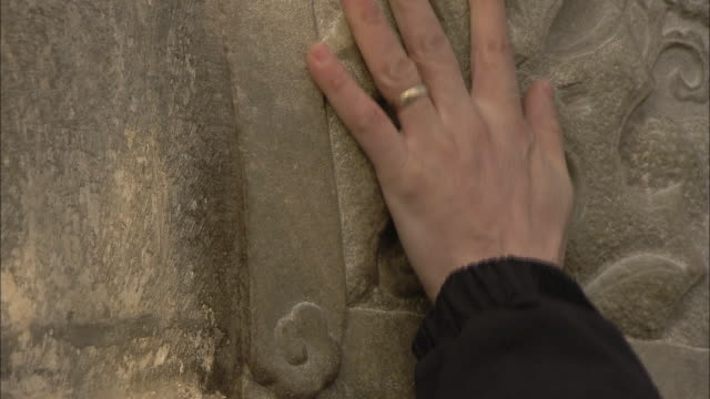 a hand touches the scrolled carvings of a bas relief wall. - bas relief stock videos & royalty-free footage
