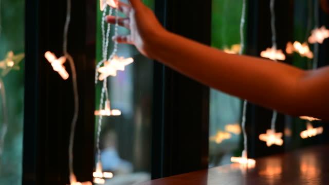 vídeos y material grabado en eventos de stock de mano tocando decoración de navidad y linterna con la vela en una ventana - decoración artículos domésticos