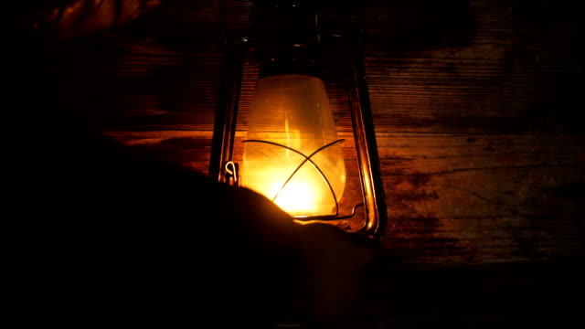 hand turn on lantern lamp at night - start button stock videos & royalty-free footage