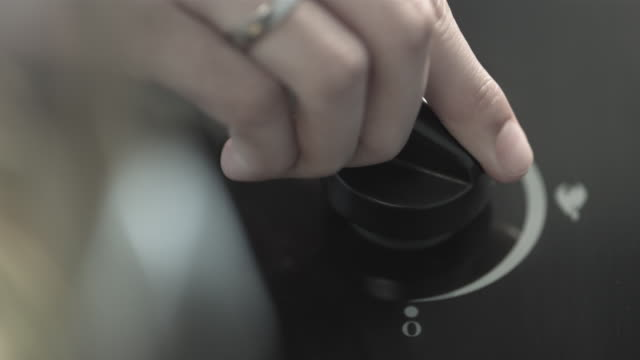 Hand turning gas volume knob on stove.