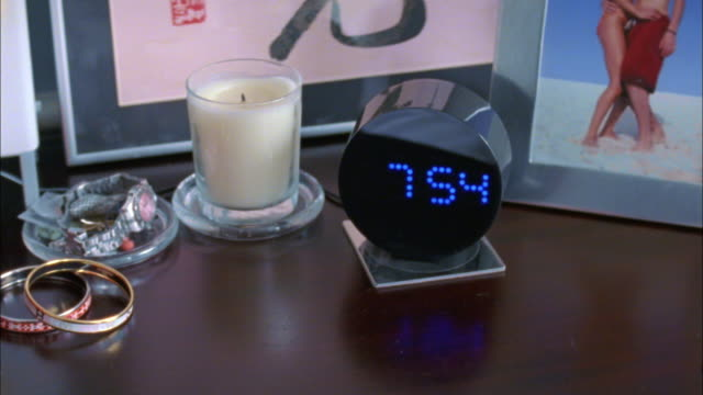 CU Hand turning off alarm clock on bedside table, New York City, New York, USA