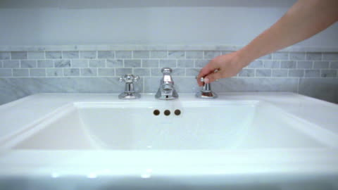 ms hand turning water on and off at sink, new york city, new york, usa - waschbecken stock-videos und b-roll-filmmaterial