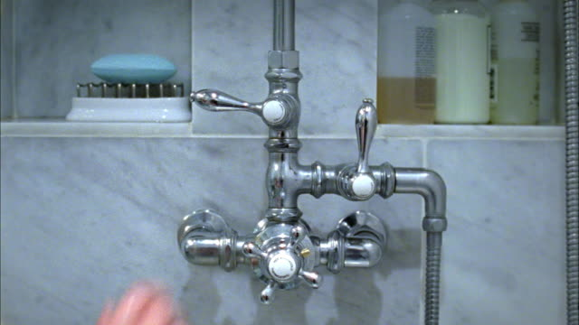 cu hand turning water on in shower, new york city, new york, usa - zapfen stock-videos und b-roll-filmmaterial