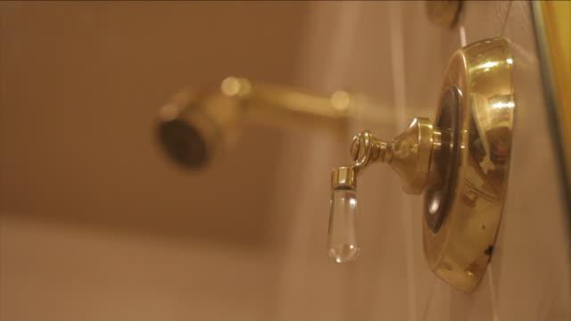 vídeos de stock e filmes b-roll de a hand turns a faucet and a shower head starts spraying water. - tomar banho