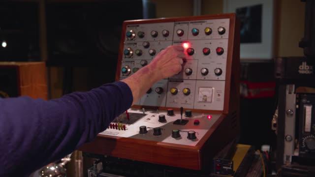 a hand turns dials on a retro audio effects unit - menschliche gliedmaßen stock-videos und b-roll-filmmaterial