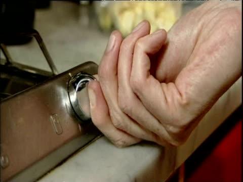Hand turns knob gas flame ignites on hob; 2006