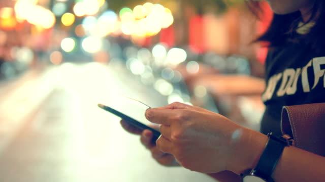 vídeos de stock e filmes b-roll de hand typing on a smartphone at night - só meninas adolescentes