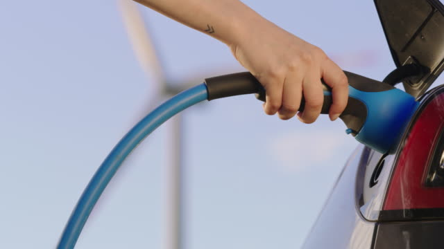 slo mo hand unplugging an ev plug from a car being charged with green energy from wind turbines - electrical plug stock videos & royalty-free footage