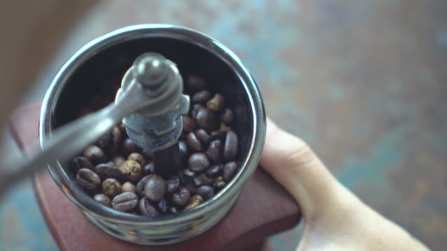 hand use old vintage coffee grinder with coffee beans. - macinare video stock e b–roll