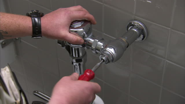 vidéos et rushes de a hand uses a screwdriver on a water pipe for a toilet. - plombier