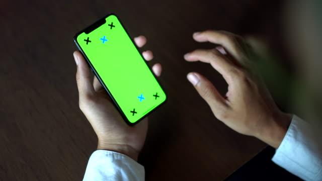 vidéos et rushes de main à l'aide de l'écran iphone vert - tenir