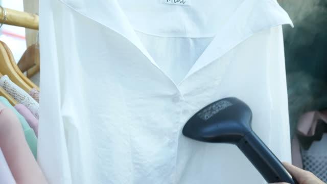 vidéos et rushes de main à l'aide de vêtements fer avec fer à vapeur dans le magasin de vêtements - fer